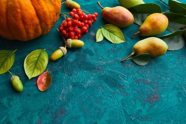 Décor d'automne festif de citrouilles, poires, feuilles, glands et baies sur fond vert, automne à plat, composition d'automne, récolte, jour de thanksgiving.