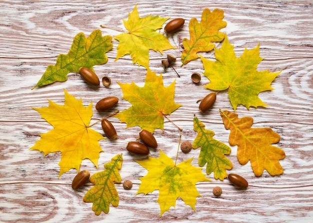 Décor d'automne de feuilles et de glands sur un fond en bois texturé. composition d'automne à plat