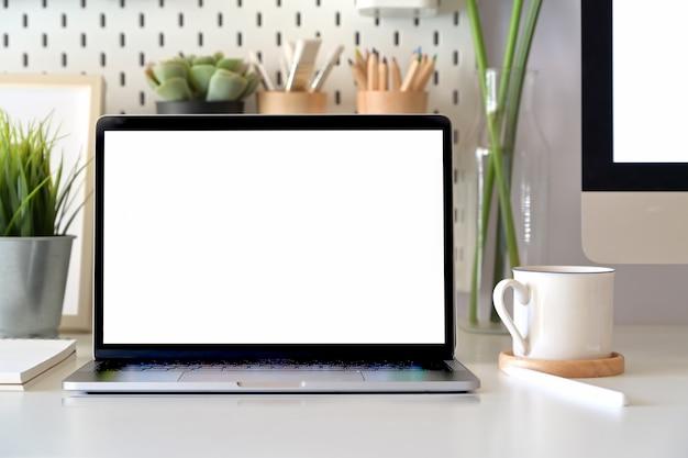 Décor de bureau avec maquette d'ordinateur portable à écran blanc. espace de travail minimal