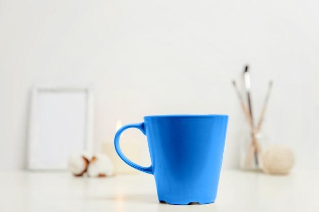Décor éco naturel avec une tasse de café colorée dans la couleur tendance de l'année 2020 classic blue près du lieu de travail blanc. couleur macro lumineuse. espace de travail de style scandinave hygge avec tasse de boisson chaude.