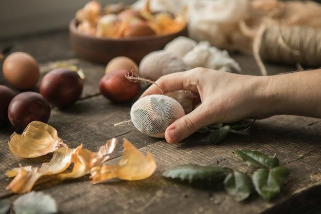 Décor écologique. œufs de pâques bouillis dans des pelures d'oignons. la main féminine tient un œuf sur une table en bois gros plan.