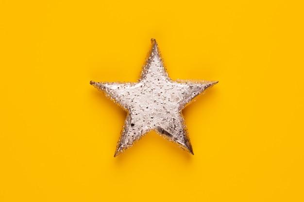 Décor d'étoile de noël sur fond de couleur jaune.