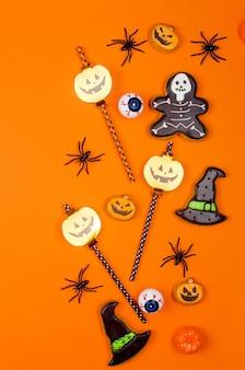 Décor de fête d'halloween boire des pailles, des citrouilles, des chauves-souris et des araignées sur fond de papier orange
