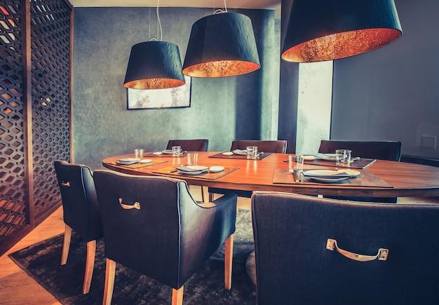 Décor intérieur élégant du restaurant mod. l'intérieur contemporain la table ronde en bois, les chaises confortables et les lampes modernes. combinaison exquise les nuances bleu royal et orange.