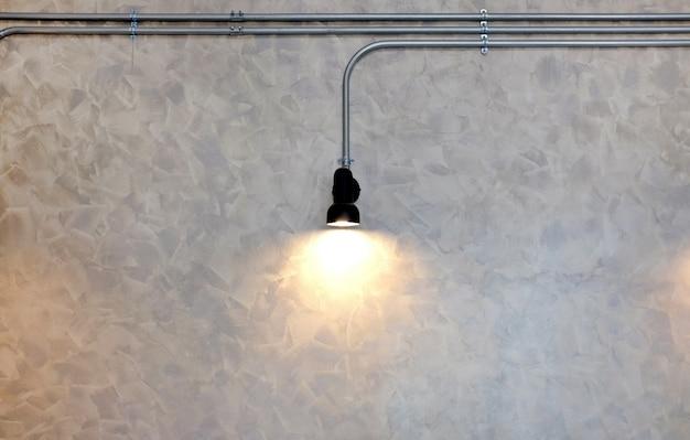Décor de lampe à suspendre sur fond de mur de carreaux gris.