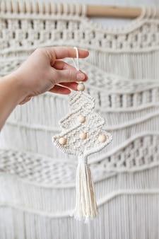 Décor macramé de noël femme main tenant un sapin de noël dans le style du décor macramé boho eco