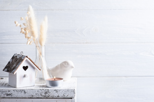 Décor à la maison dans un style scandinave avec des fleurs sèches d'herbe de pampa sur fond rustique dans un style monochrome. bougies parfumées et nichoir avec espace copie