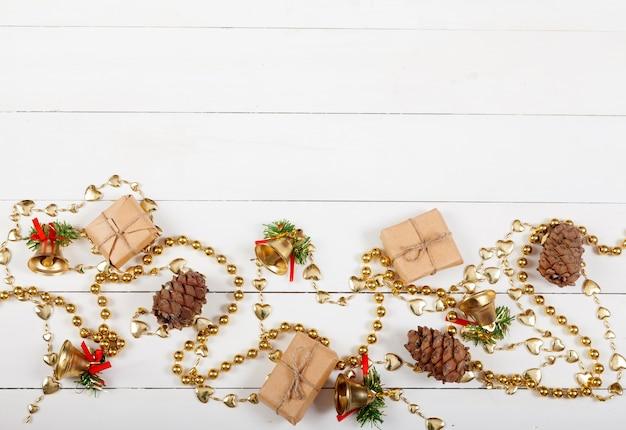 Décor de noël composé de perles, de cônes de cèdre, de cadeaux et de cloches.