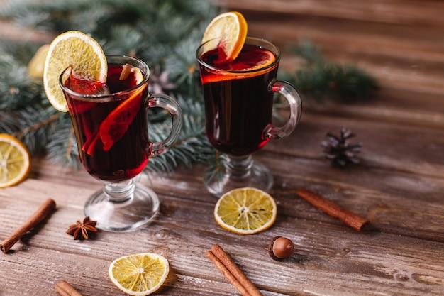Décor de noël et du nouvel an. deux tasses de vin chaud aux oranges