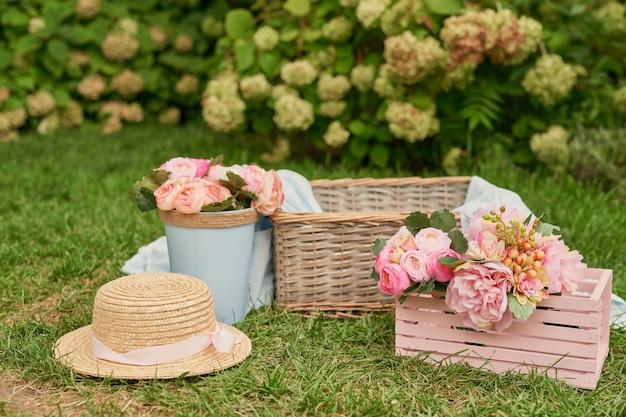 Décor de pique-nique avec des fleurs roses, un panier et un chapeau sur l'herbe en été dans le jardin