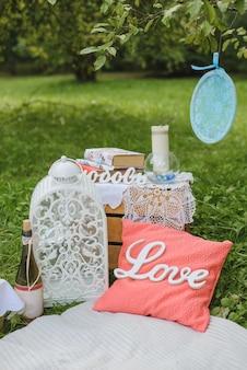 Décor de pique-nique romantique pour deux: un oreiller, une bouteille de vin, une lanterne blanche, des livres et des bougies sur une couverture.