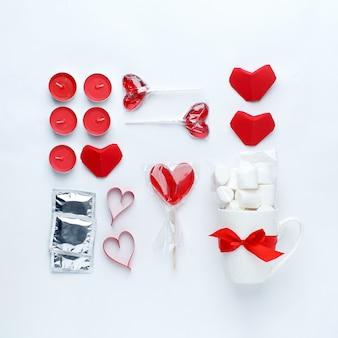Décor rouge, douceur, coeur rouge, préservatifs sur fond blanc.