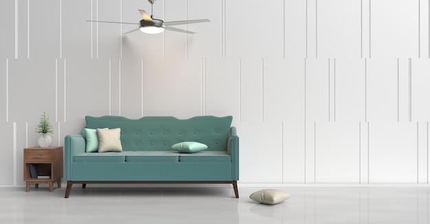 Décor de salle blanche avec canapé vert, oreiller vert et crème, livre, table de chevet en bois, ventilateur de plafond.