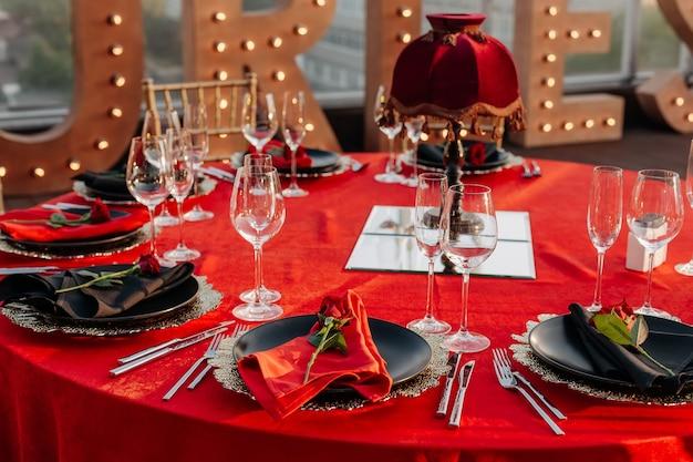 Décor de table élégant assiettes nappe rouge avec serviettes et couverts verres roses fraîches