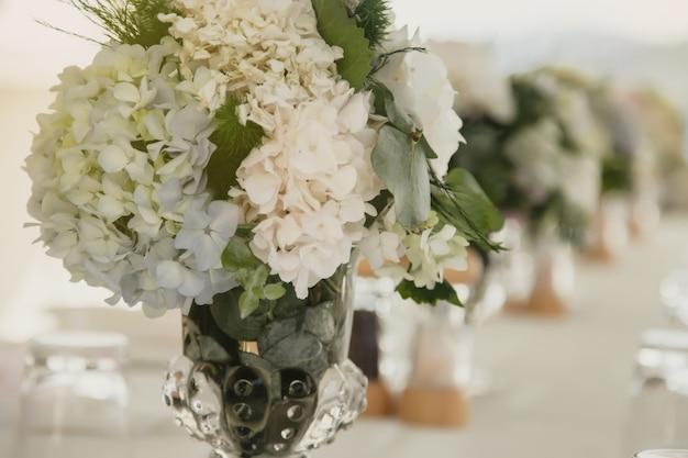 Décor de table de mariage à l'air frais sur fond de mer. décorations de table florales pour les vacances et le dîner. servir pour des vacances, un événement, une fête ou une réception dans un restaurant en plein air. bannière pour le site