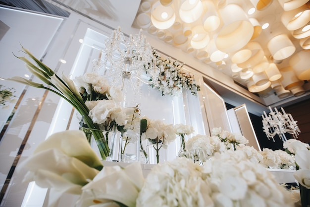 Décor de table de mariage romantique avec de grands bouquets floraux luxuriants, y compris des roses blanches ranunc ...