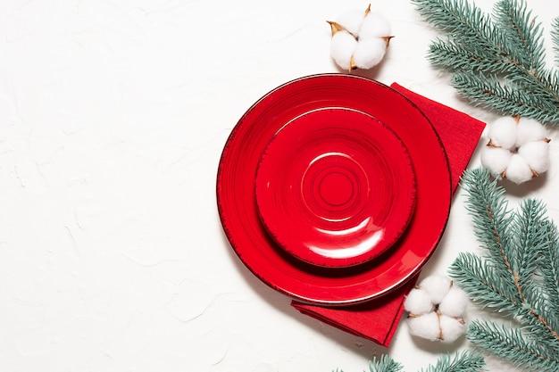 Décor de table de noël ou du nouvel an avec assiettes rouges, serviette, branches de sapin et fleurs de coton