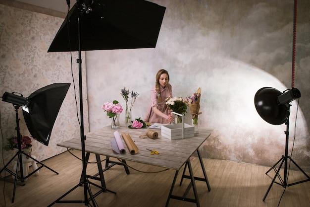 Le décorateur fait un bouquet de fleurs au studio. jeune fille fait un ornement de fleurs blanches dans un atelier. séance photo dans les coulisses