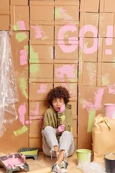 Décorateur de femme créative émotionnelle effrayée est assis sur le sol