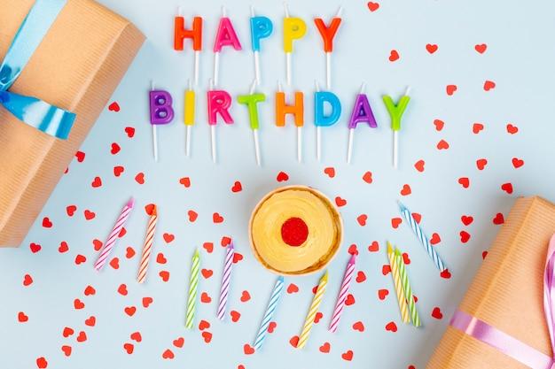 Décoration d'anniversaire vue de dessus avec des cadeaux et des bougies