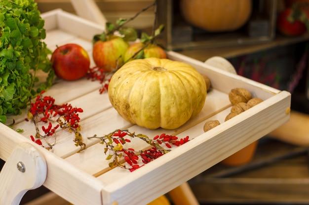 Décoration d'automne citrouille, noix, pommes sur une table en bois. concepts d'automne