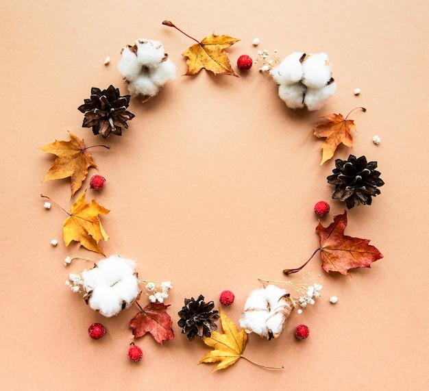 Décoration d'automne avec des fleurs en coton et des feuilles d'érable sèches en forme de cercle sur un fond marron