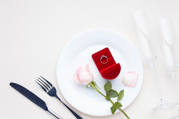 Décoration avec bague de fiançailles dans une boîte rouge