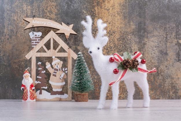 Décoration en bois de noël et jouet de cerf sur une surface blanche.
