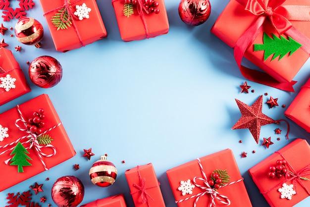 Décoration de boîte cadeau noël rouge sur fond bleu pastel.