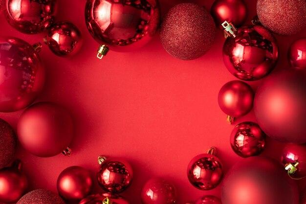 Décoration de boules de noël rouge sur fond rouge avec espace de copie. carte de voeux de nouvel an. style minimal. mise à plat.