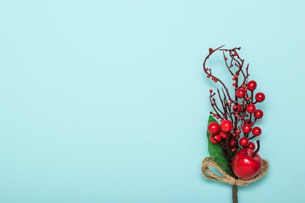 Décoration d'une brindille avec des pommes rouges sur un mur bleu. réveillon de nouvel an.