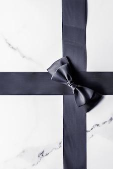 Décoration de cadeaux de vacances et concept de promotion des ventes ruban de soie noire et arc sur la surface en marbre flatlay