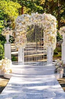 Décoration de cérémonie de mariage. arc blanc avec des fleurs. fond de parc verdoyant. fête d'été.