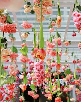 Décoration de cérémonie de mariage avec beaucoup de fleurs artificielles suspendues au plafond.