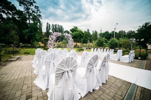 Décoration d'une cérémonie en plein air dans un jardin verdoyant, une arche de fleurs fraîches, un chemin blanc pour les jeunes mariés, des chaises en tissu blanc
