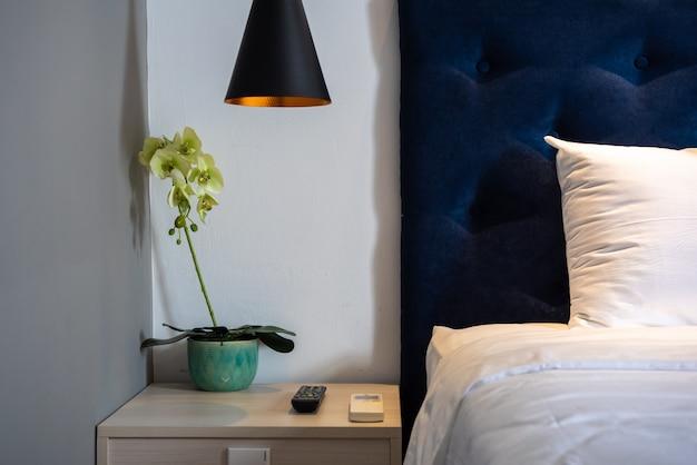 Décoration de la chambre avec table, lampe suspendue, fleur d'orchidée dans le vase et lit au fond du mur.