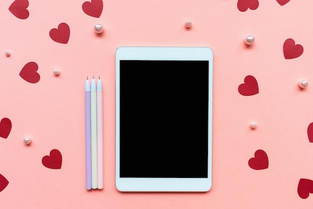 Décoration de confettis coeurs en papier rouge, perles blanches, stylos et tablette sur fond rose.