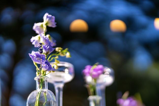 Décoration décorative de la table de fête. vases en verre et fleurs fraîches. décoration de vacances en plein air