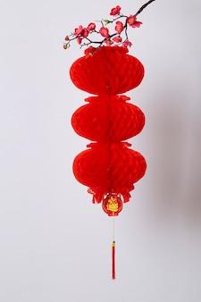 Décoration du nouvel an chinois lanterne rouge et fleur de pêcher sur un mur blanc texte caractères chinois signifie riche