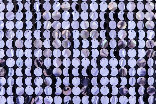 Décoration d'événement sur la zone photo. mur de presse composé de nombreuses paillettes rondes scintillantes. résumé fond clair de guirlandes