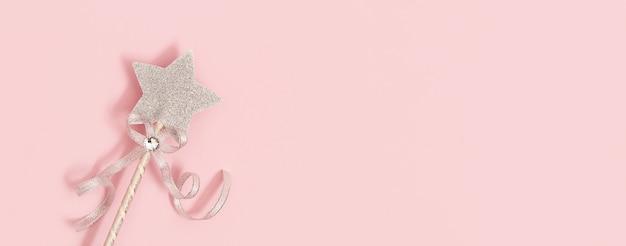 Décoration festive, baguette magique, étoile argentée brillante sur rose
