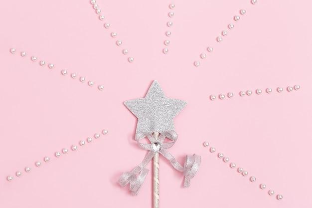 Décoration festive étoile d'argent brillant avec des paillettes sur fond rose tendre