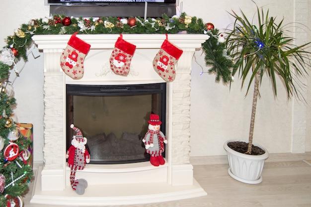 Décoration festive de l'intérieur du salon avec une cheminée, des chaussettes et des gnomes sont accrochés.