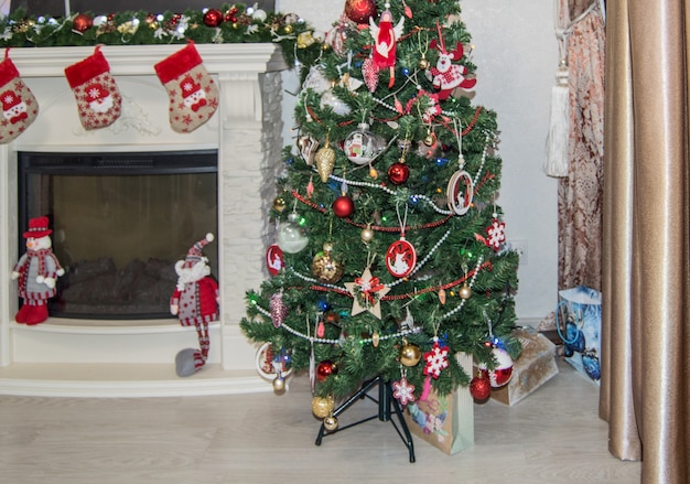 Décoration festive de l'intérieur du salon, avec une cheminée, décorée de chaussettes cadeaux, un sapin de noël avec des jouets
