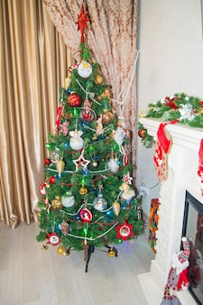 Décoration festive de l'intérieur du salon, avec un sapin de noël avec des jouets et une étoile