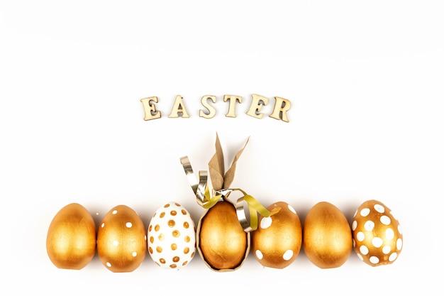 Décoration festive de pâques. vue de dessus des oeufs de pâques colorés avec de la peinture dorée et inscription en anglais joyeuses pâques.