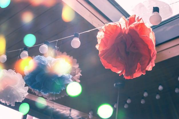 Décoration festive de pompons en papier et d'une guirlande d'ampoules. abstrait