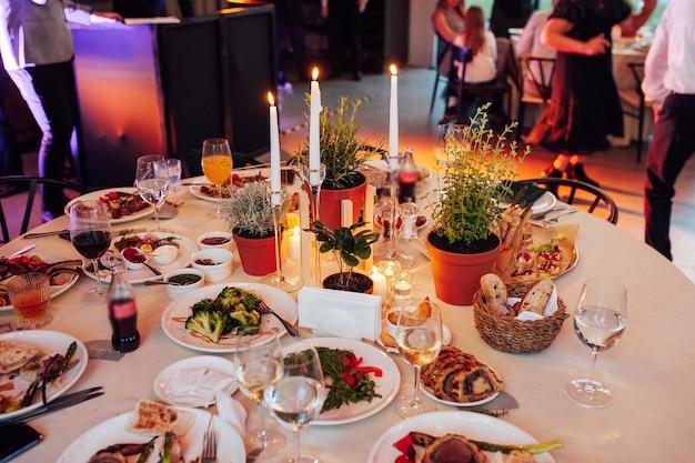 Décoration de fleurs et de bougies pour un mariage sur fond d'invités dansants