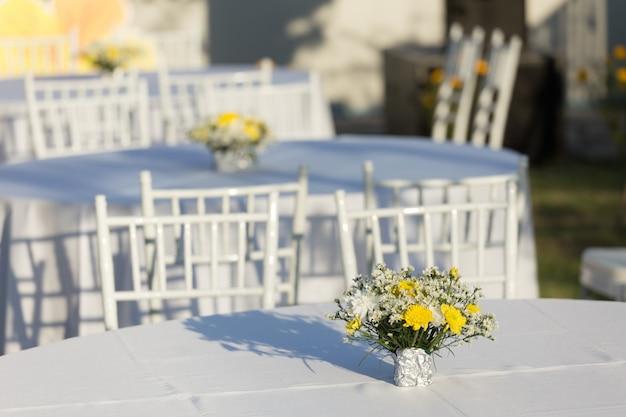 Décoration de fleurs sur une table blanche en plein air lors d'une réception de mariage