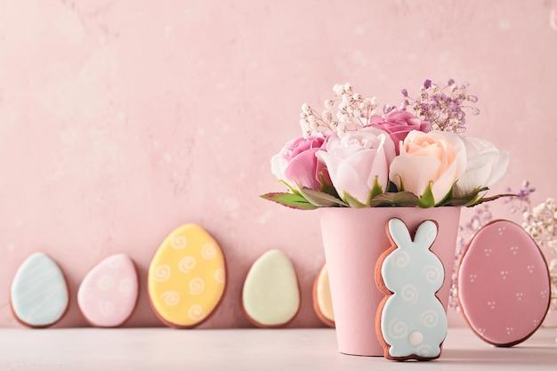 Décoration de fond de pâques avec un beau bouquet de fleurs roses roses dans un vase, des œufs de pâques, un lapin et un poussin sur une table de fond rose. concept de pâques avec espace de copie.